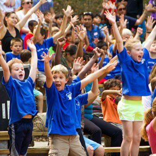 Photo of elementary school children dancing during a performance at Children's Theatre-in-the-Woods