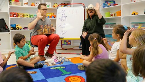 Photo of a Wolf Trap Teaching Artist and teacher working together in the classroom